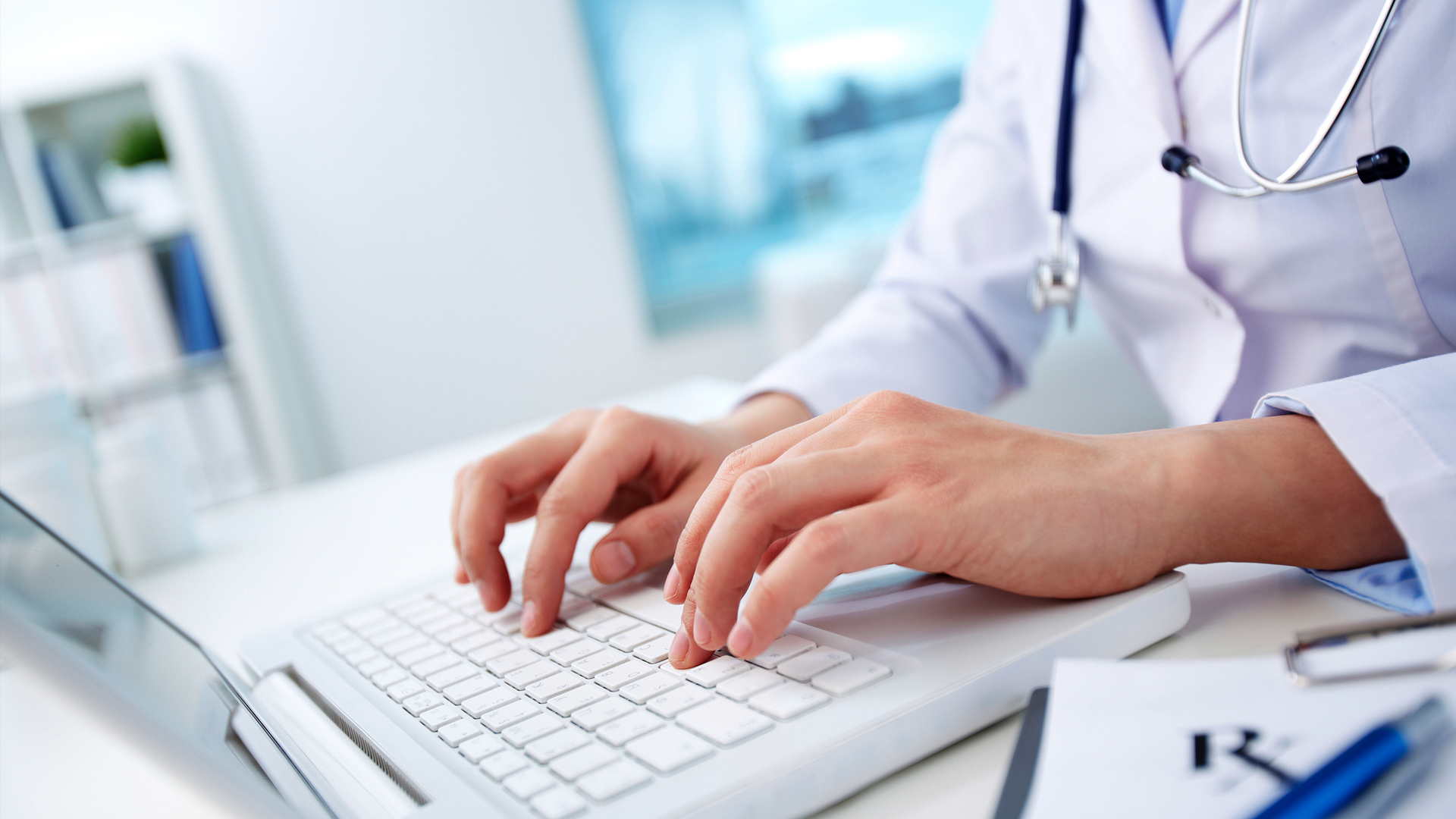 medical professional typing on a laptop keyboard