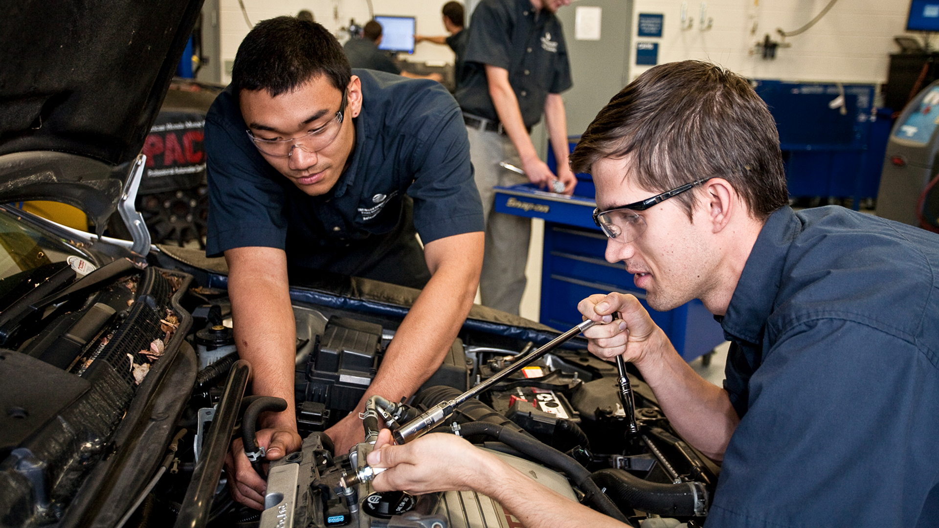 two male students working on a car engine