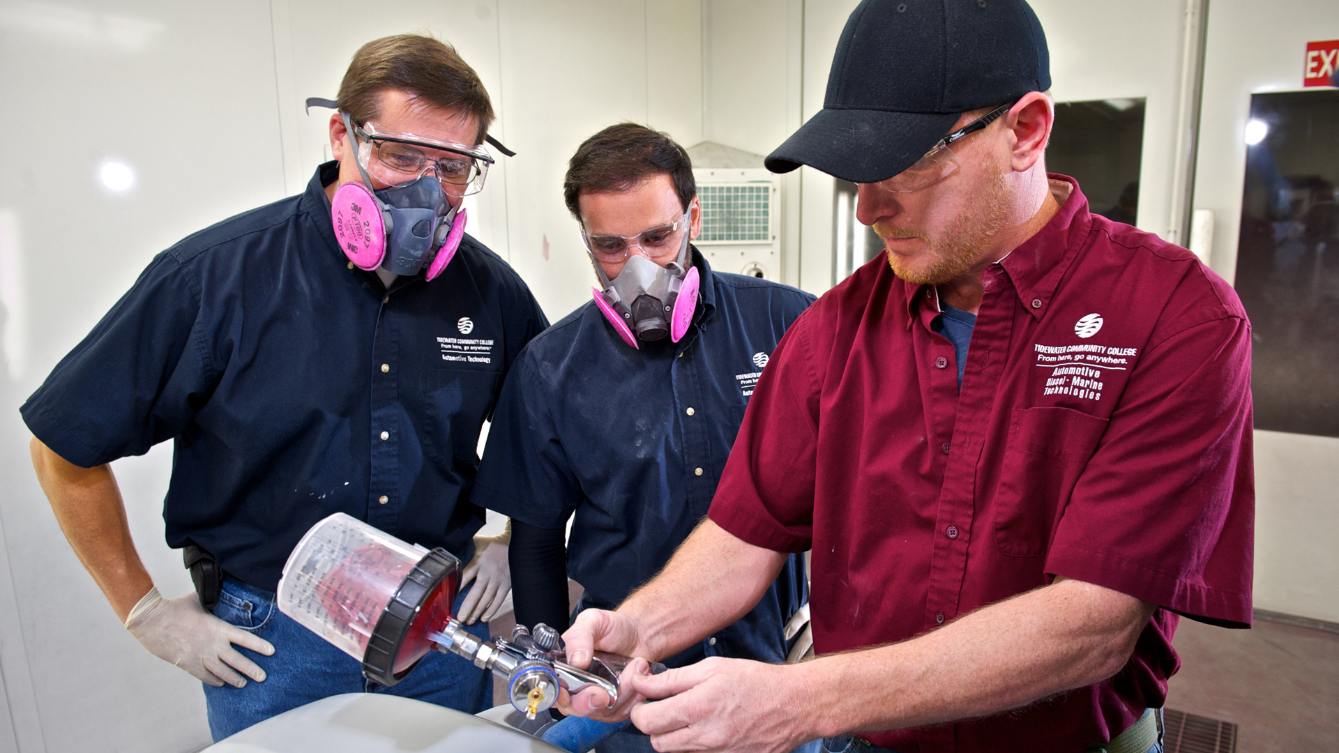 Two students and an instructor work with collision repair equipment